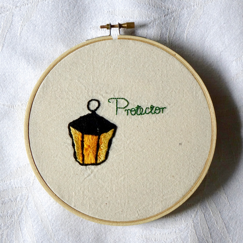"""""""Protector"""" embroidered in green cursive with a glowing metal lantern."""