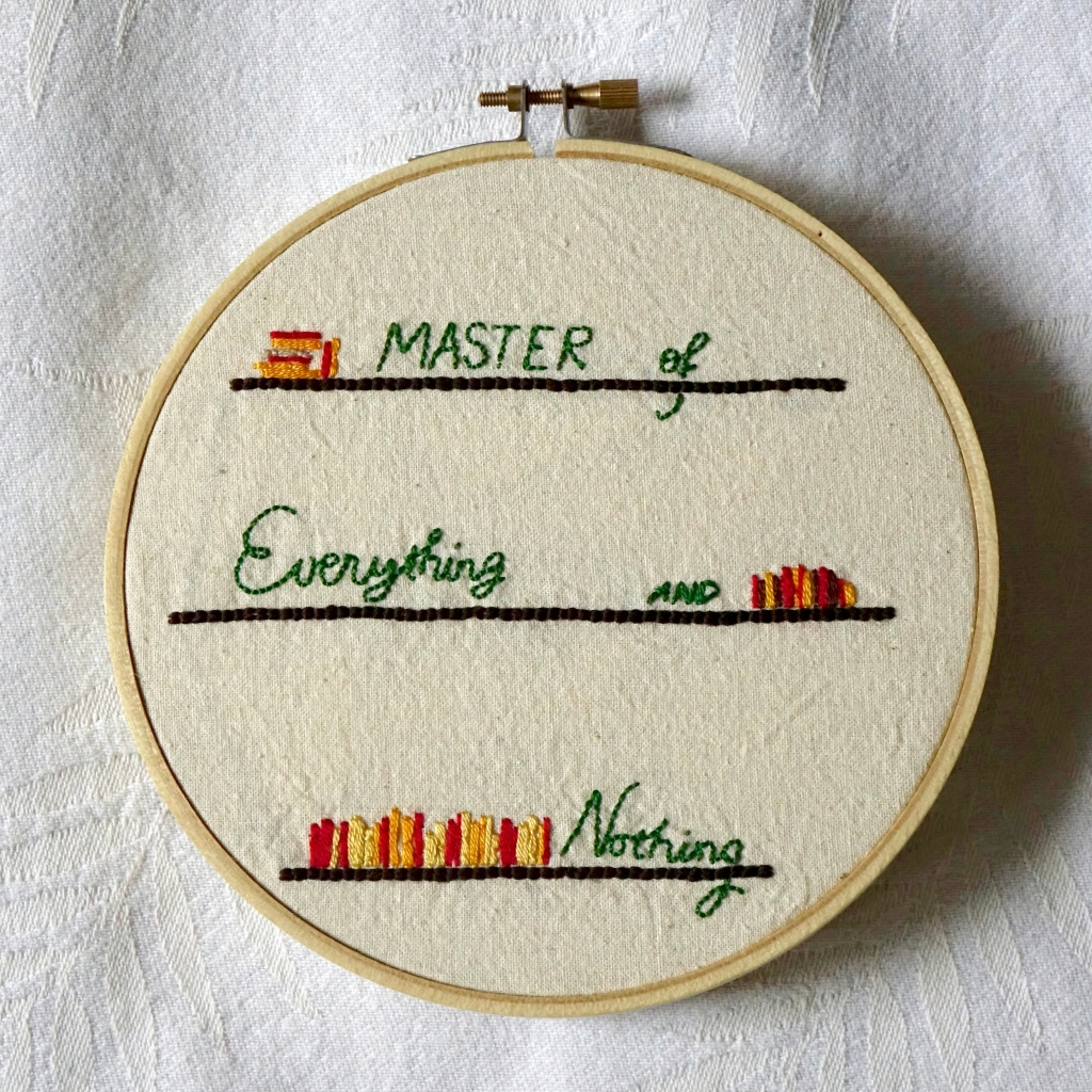 """""""Master of Everything and Nothing"""" embroidered In green script, on dark bookshelves with books the colours of autumn leaves."""