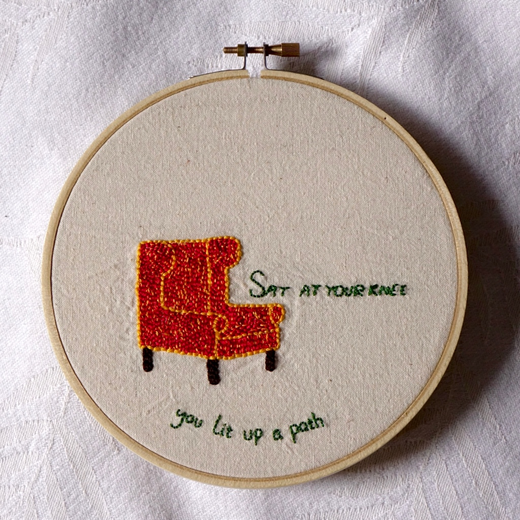 """""""Sat at your knee, you lit up a path"""" embroidered in green with a dappled red and gold wingback armchair."""