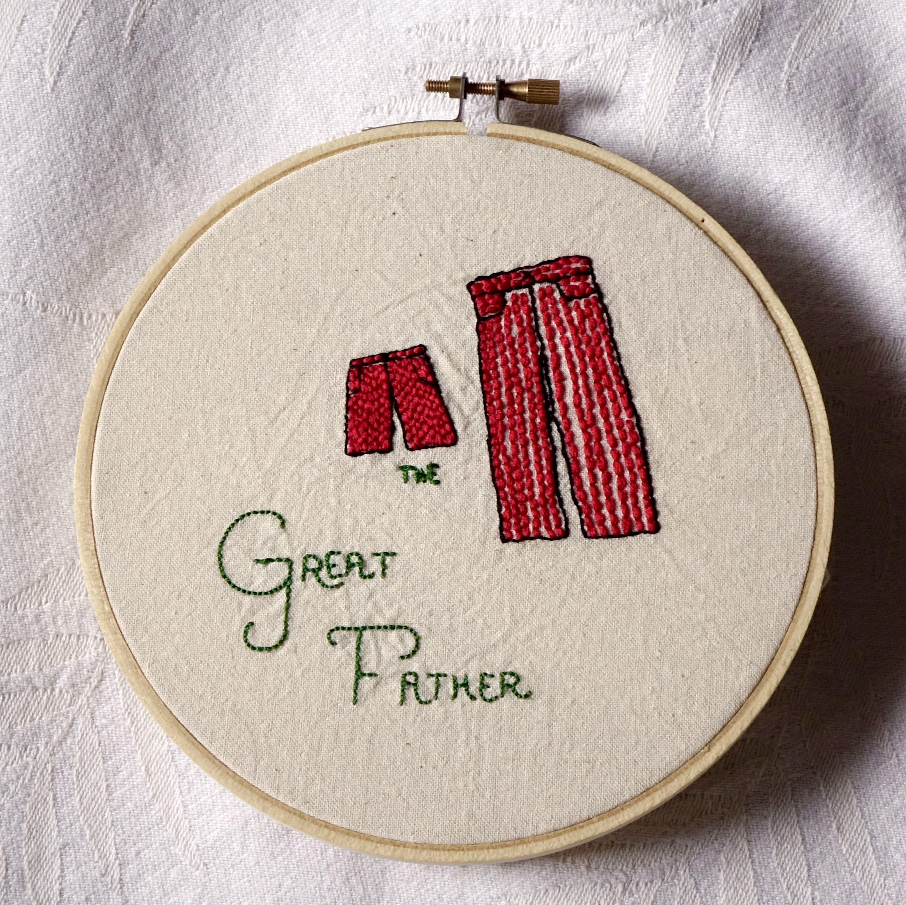 """""""The Great Father"""" embroidered in green with a child sized pair of red pants and an adult sized pair of striped red and white pants."""