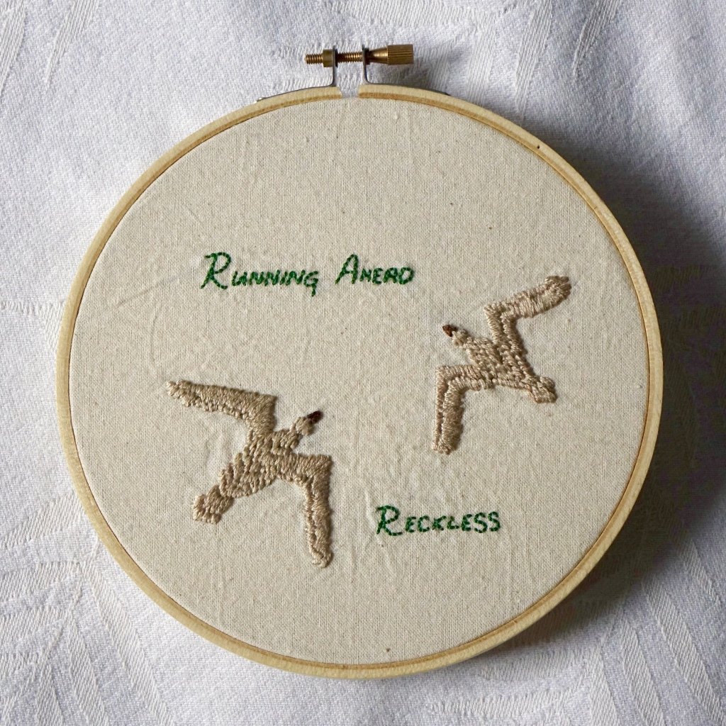 """""""Running Ahead Reckless"""" embroidered in green full capitals with two tan birds."""