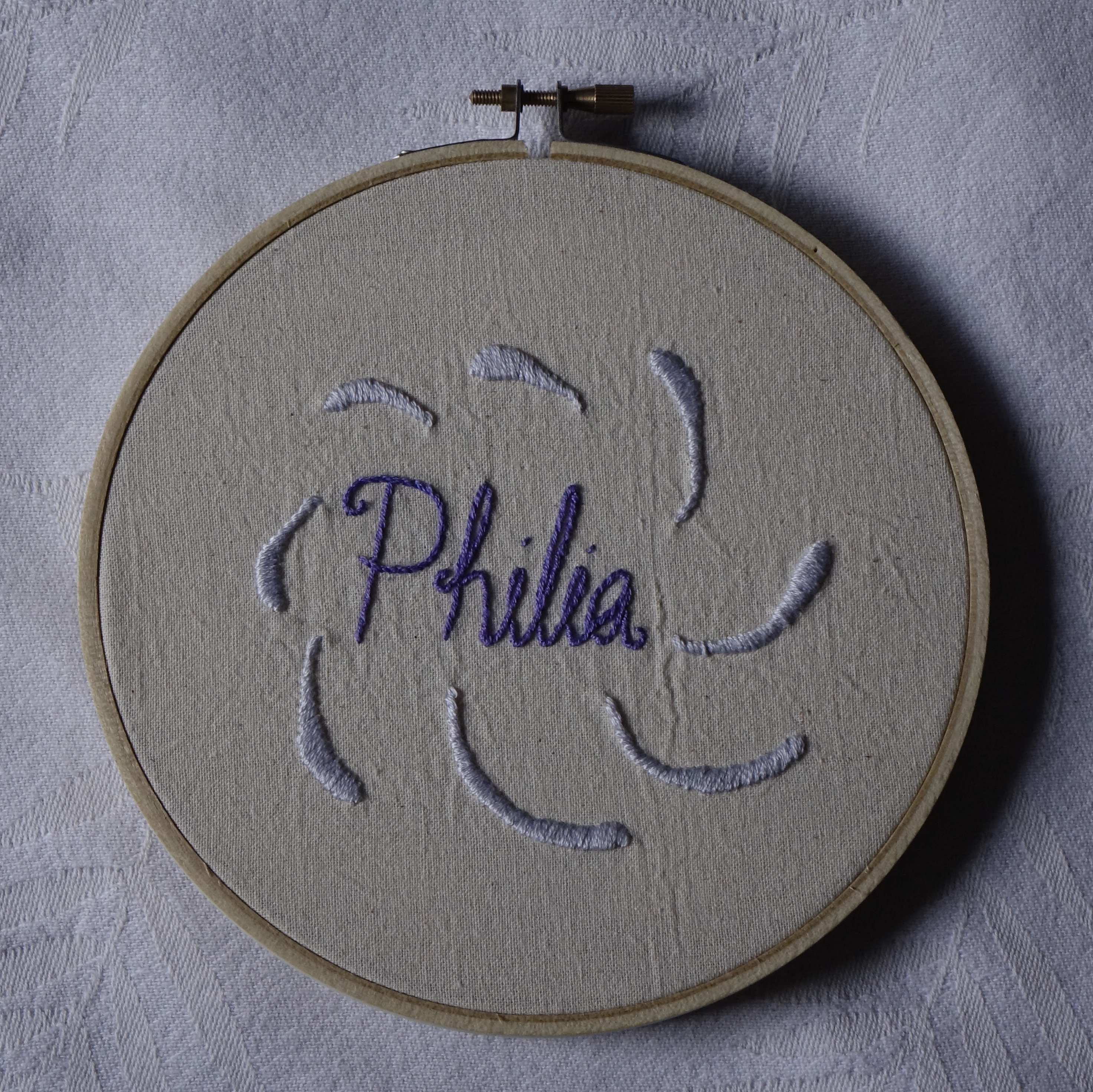 """""""Philia"""" embroidered in ornamented purple cursive, surrounded by pale purple curves."""