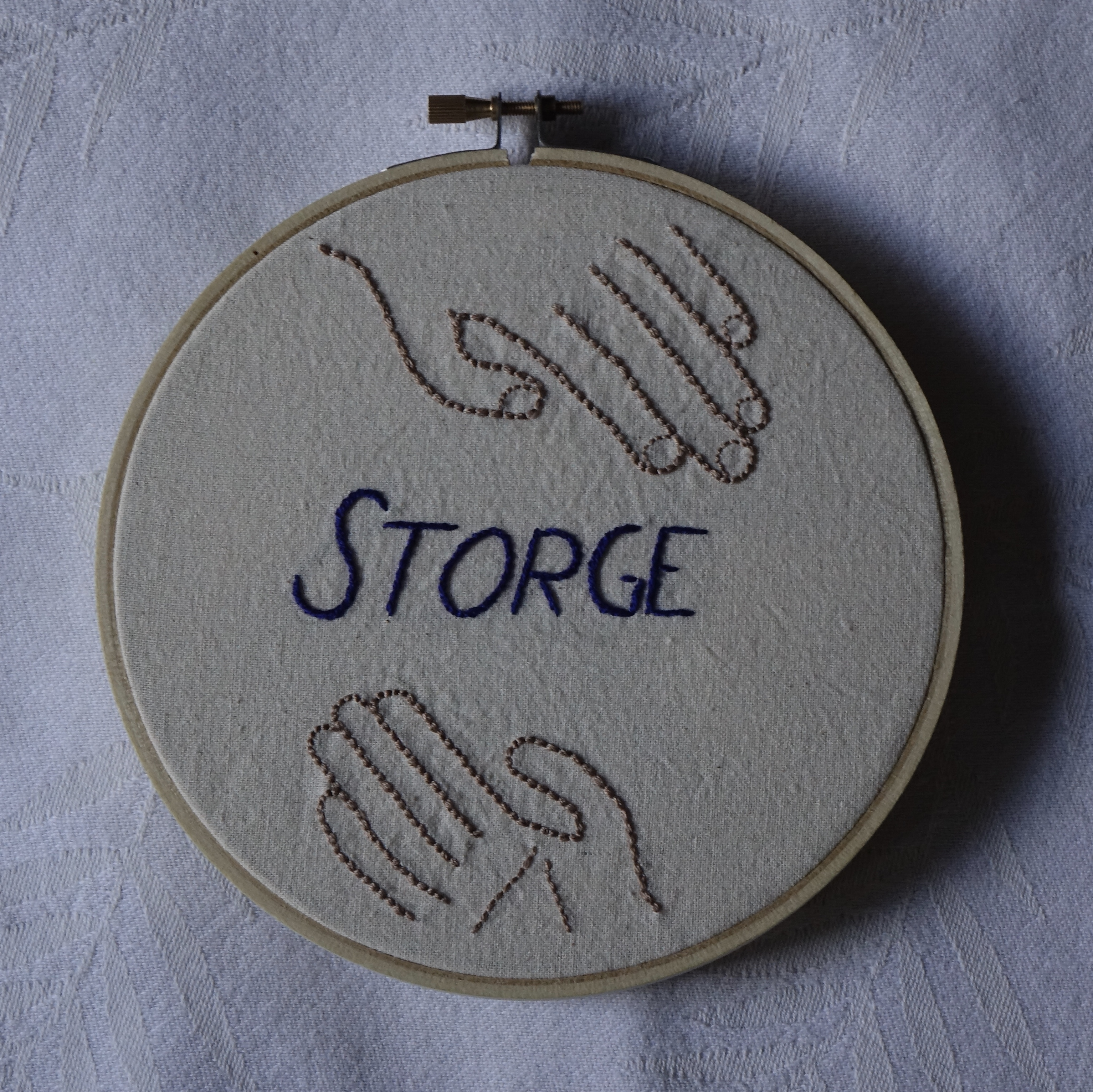 """""""STORGE"""" embroidered in dark blue italics, with two hands."""