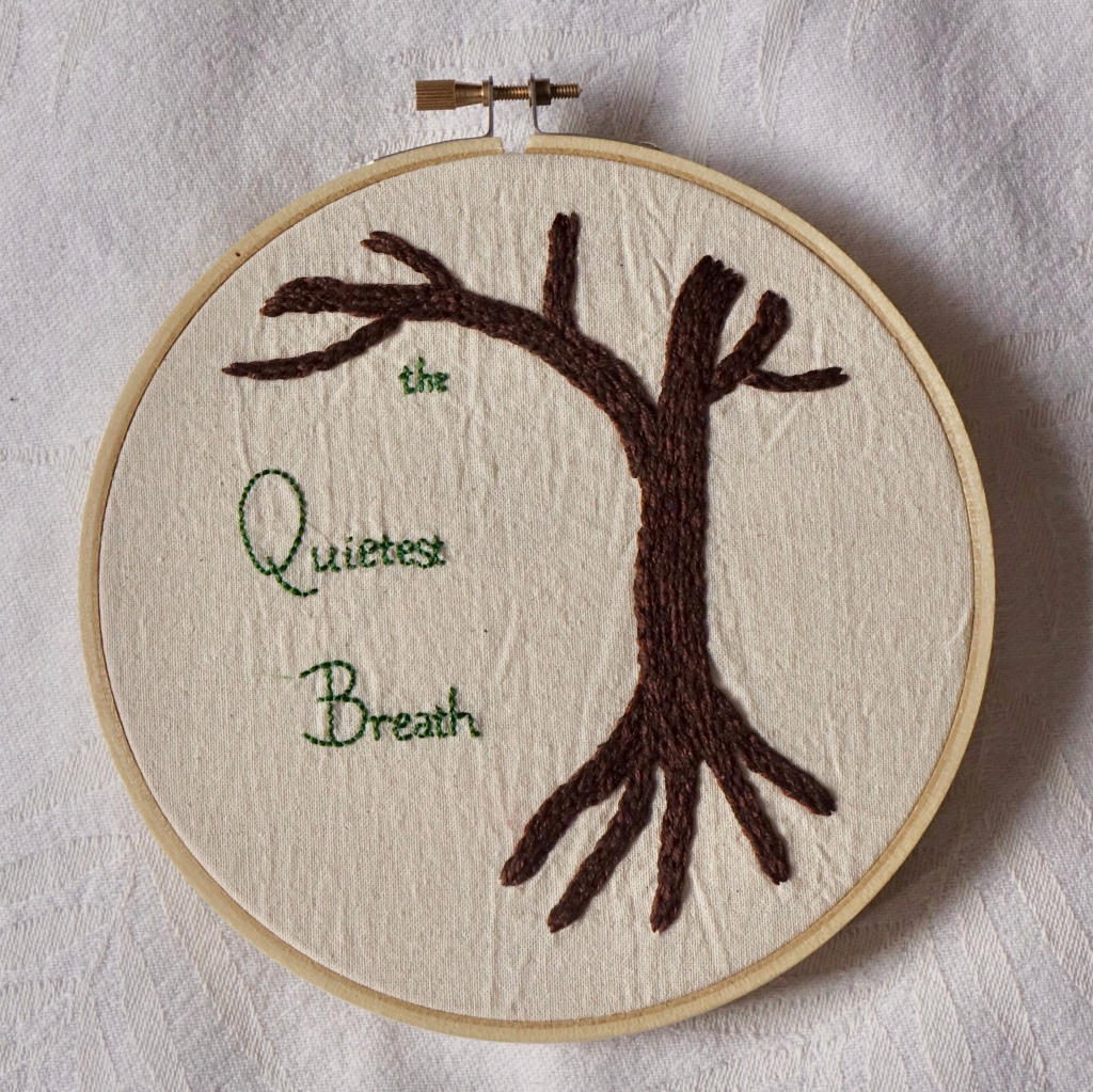 """""""the Quietest Breath"""" embroidered in green with a bare branched tree."""