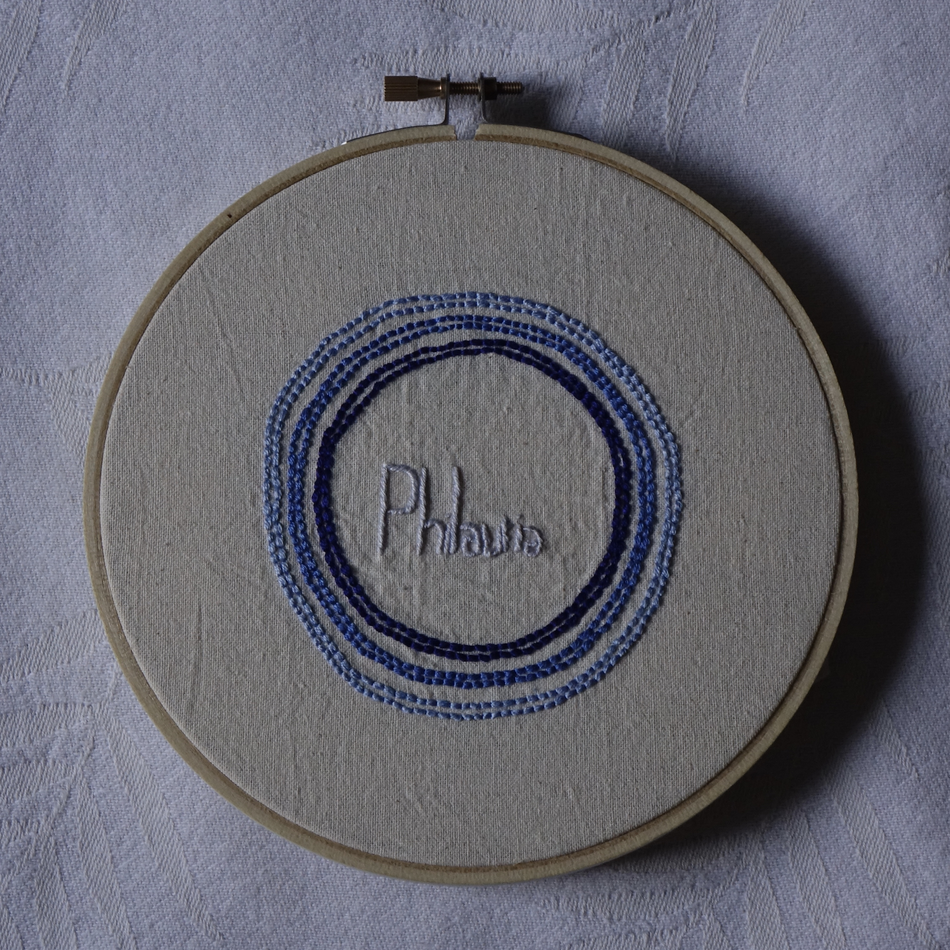 """""""Philautia"""" embroidered in pale blue print, surrounded by three concentric blue circles (palest on the outer, darkest toward the centre)."""