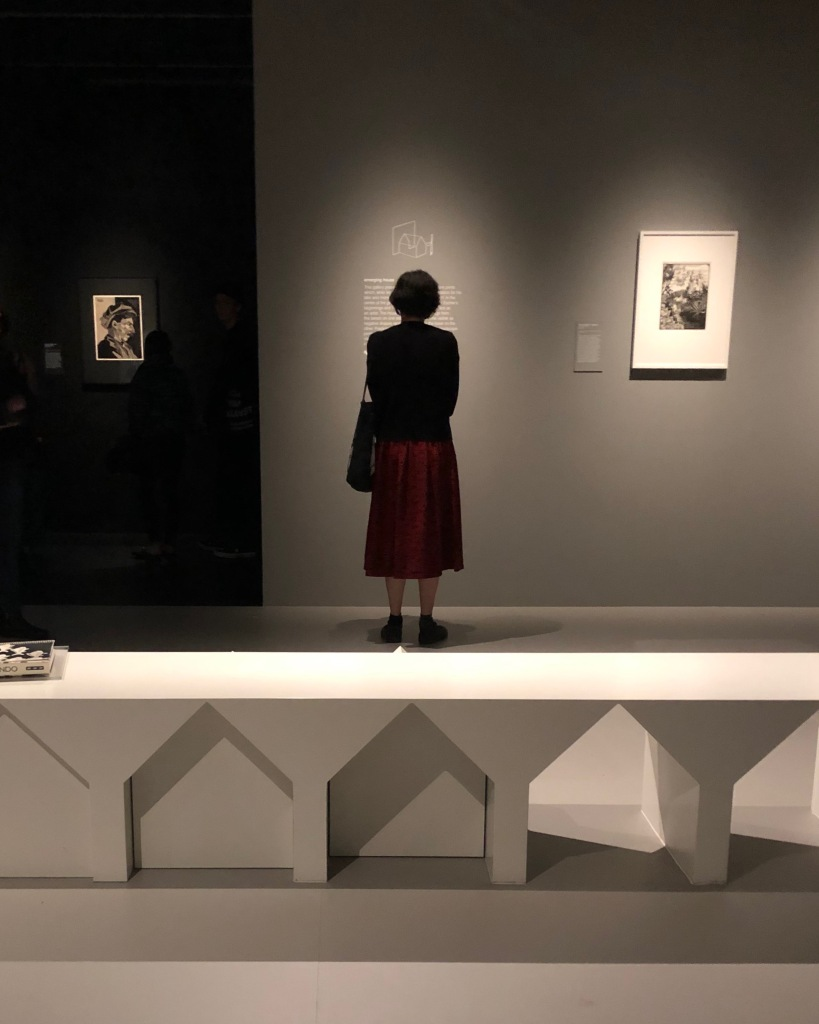 A lady in a red skirt stands in front of a spotlight splashed wall; behind her is a bench with house shapes pushed out of it.