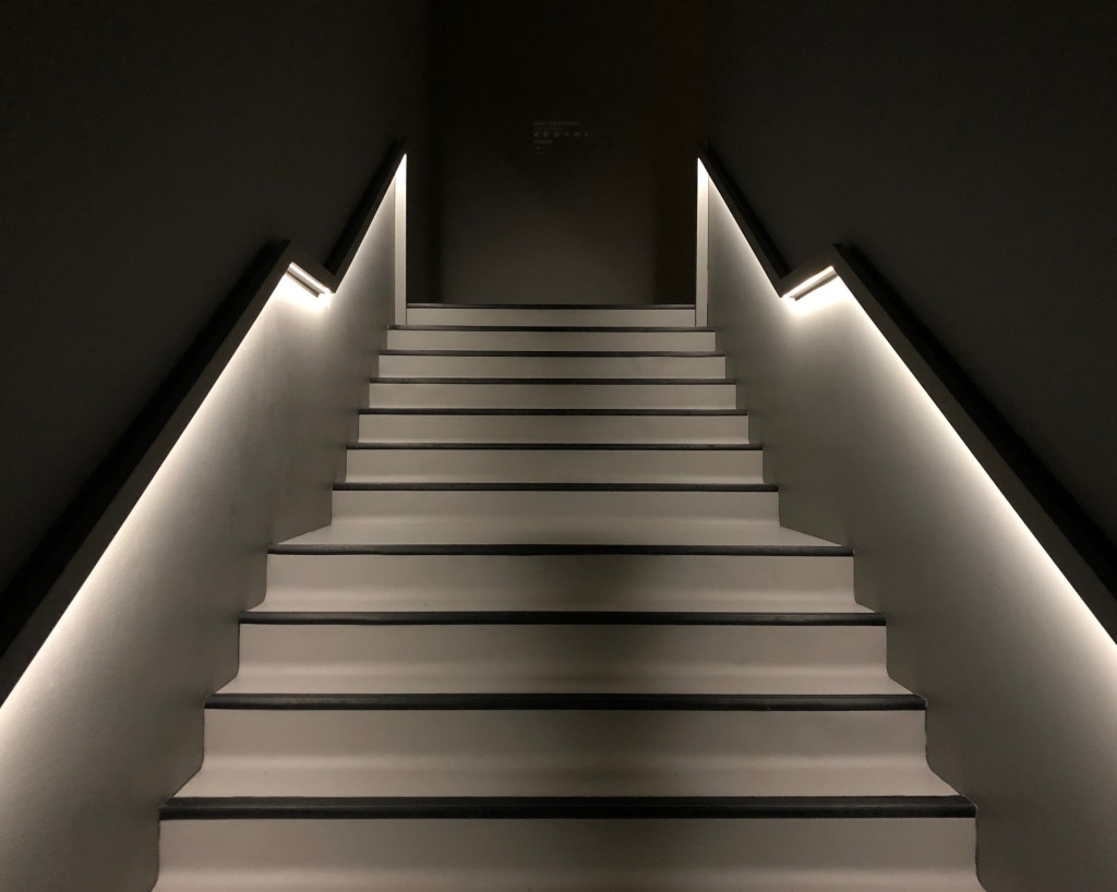 White stairs with black edges, light glowing from the handrail, against black walls.