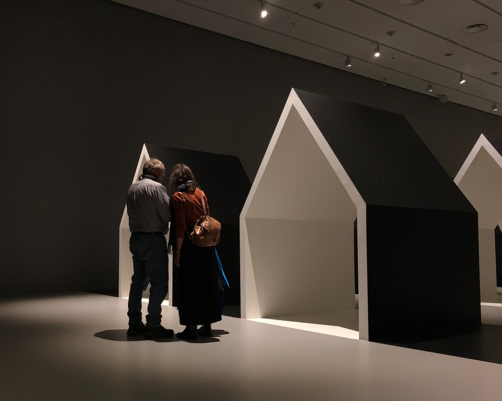 A pair stand together looking at a shared object, in front of a house frame (black outside, white inside).