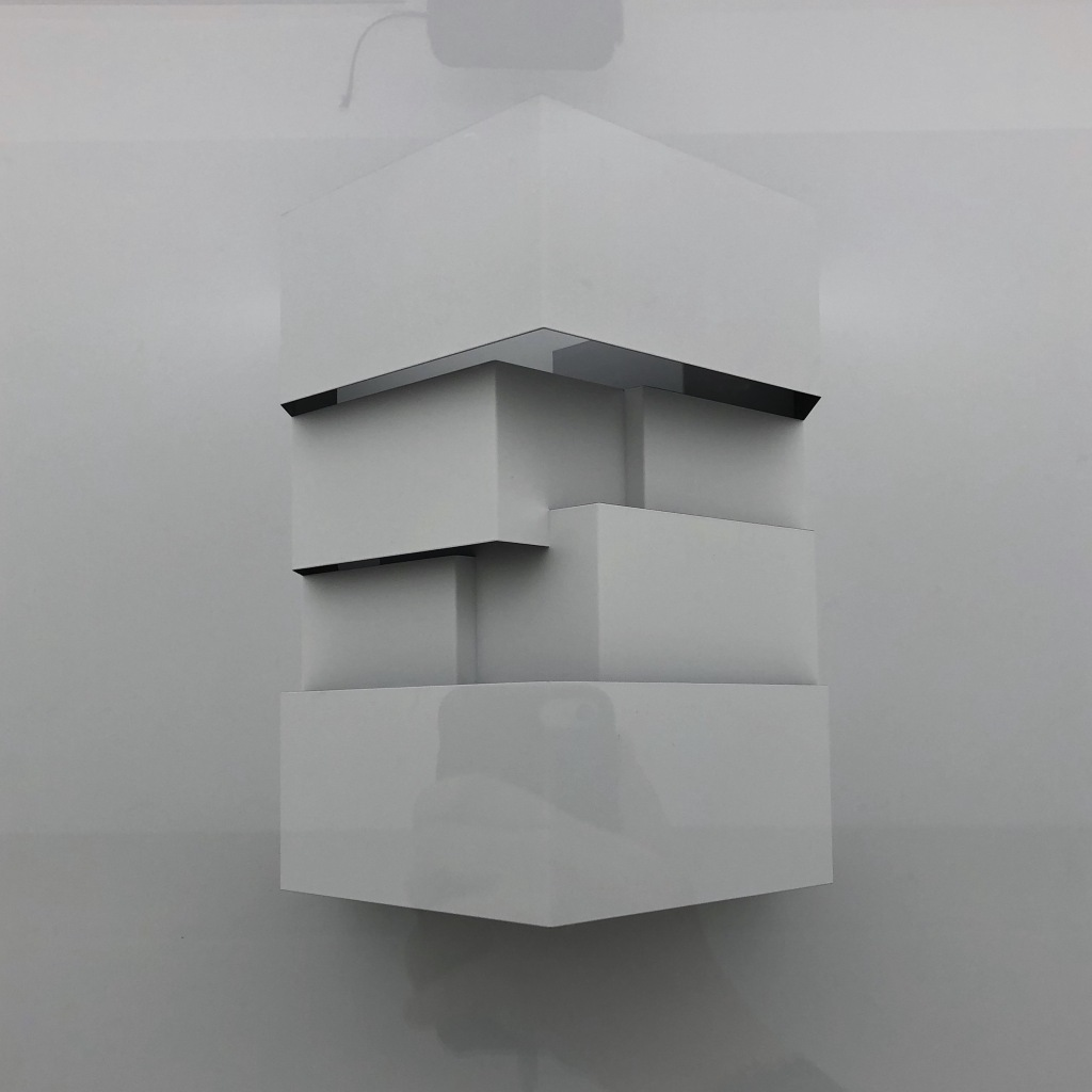 A layered white roof, against a white background, with the reflection of a hand holding a phone in the bottom third.