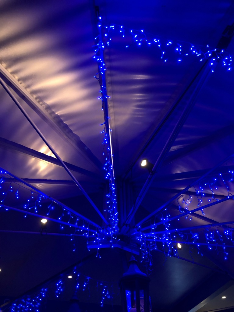 The underside of an cafe umbrella, lit with blue fairy lights.
