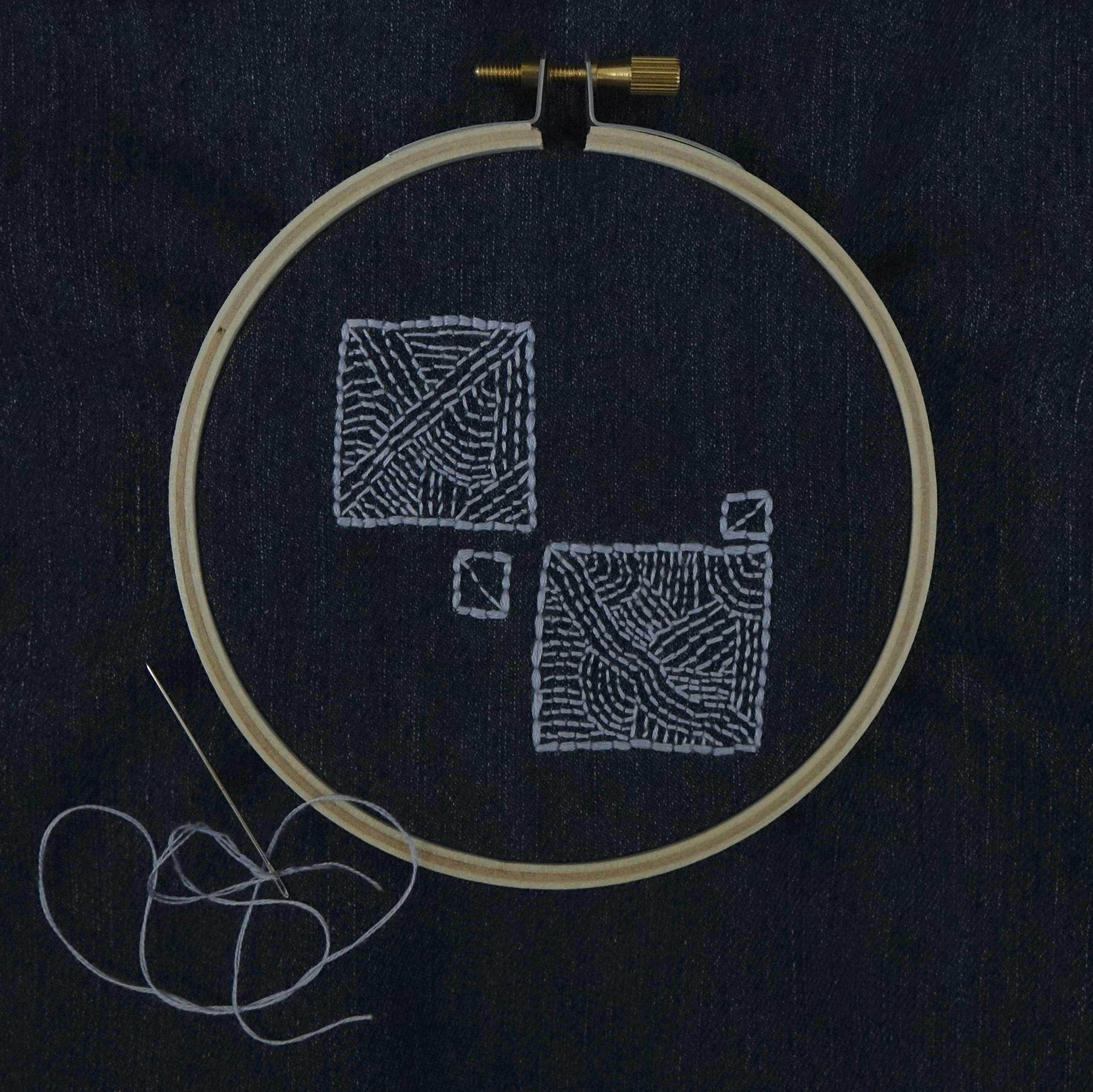 An embroidery hoop set with dark denim, two large squares aligned diagonally with two small squares on the right side centre corners.