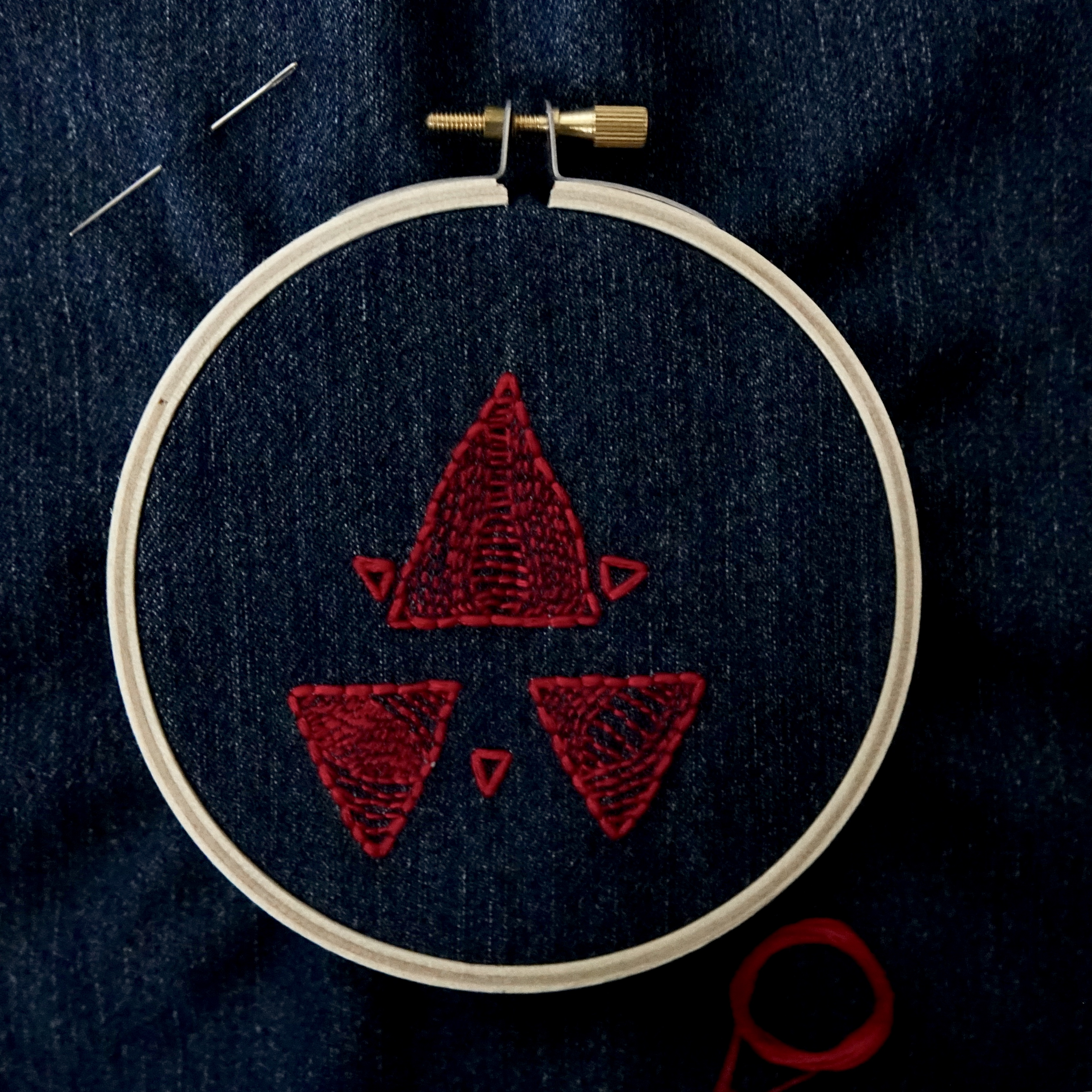 An embroidery hoop set with denim, embroidered with red triangles, shot from a mid-low angle.