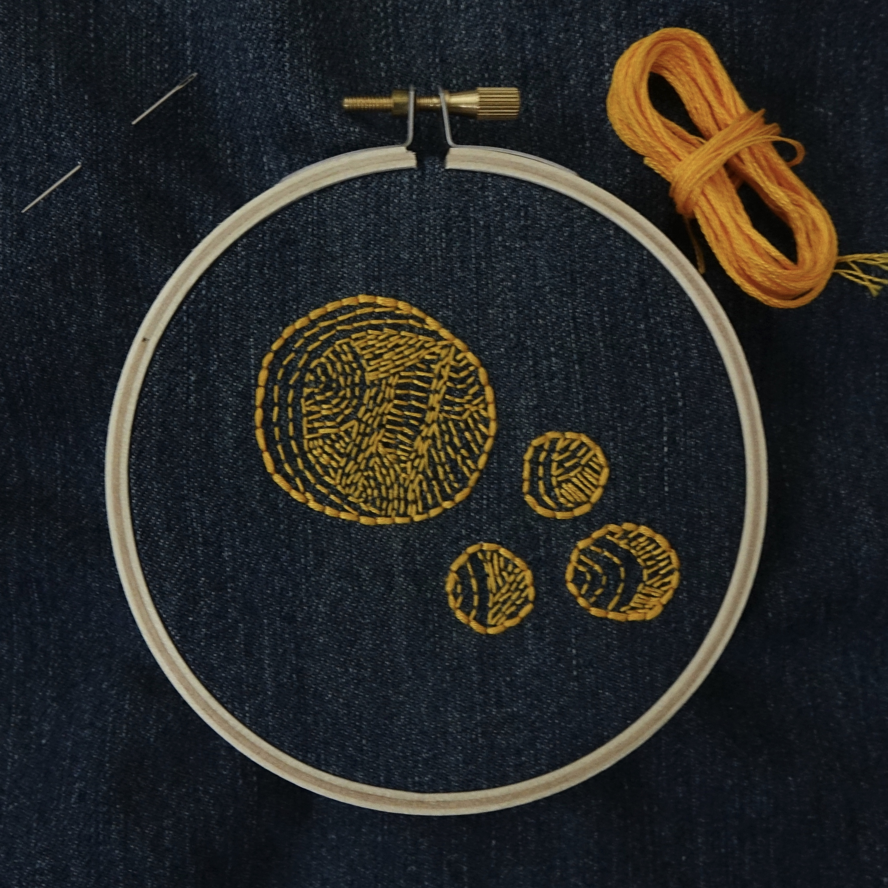 An embroidery hoop set with dark denim, one large and three small yellow-gold circles. There's a coil of floss in the top left corner and a needle threaded through the fabric on the right.