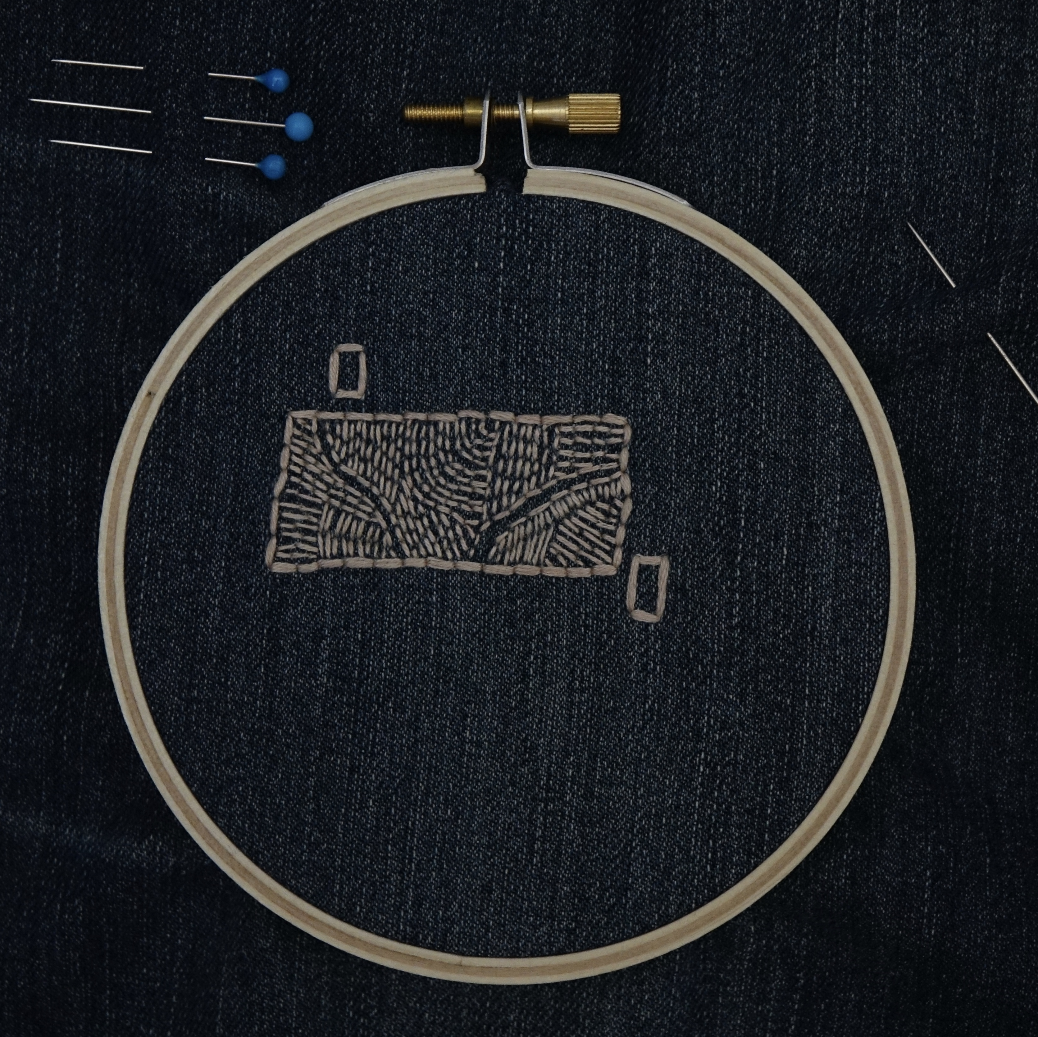 An embroidery hoop set with dark denim, a tan rectangle across the top half, with two mini rectangles on the top left and lower right corners.