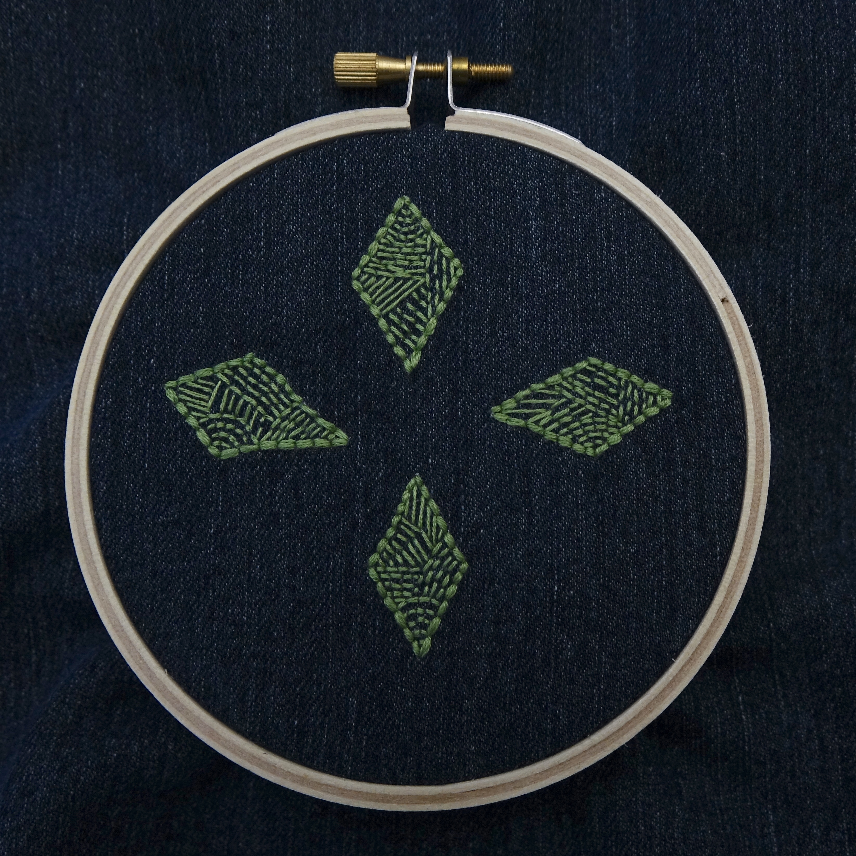 An embroidery hoop set with dark denim, four green diamonds embroidered in a compass pattern.