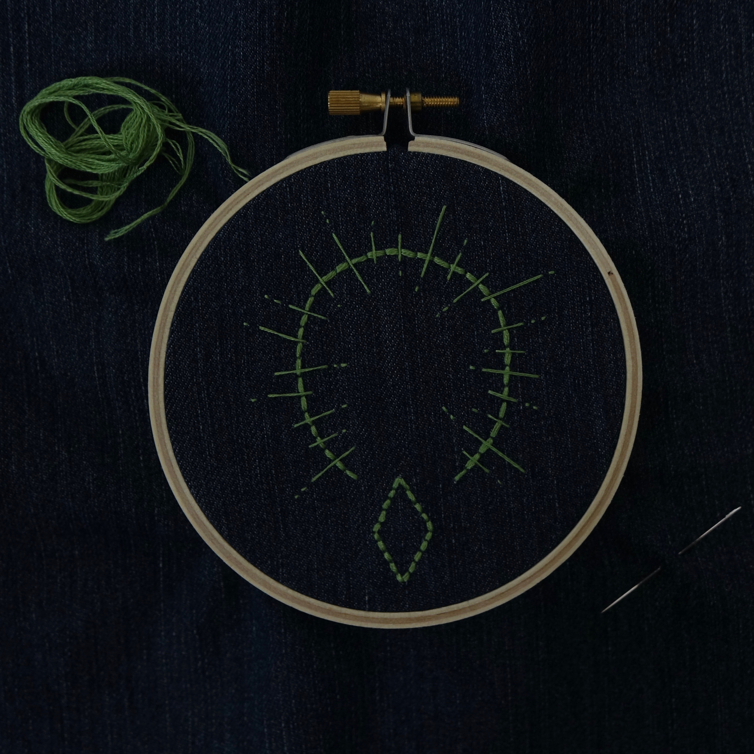 An embroidery hoop set with dark denim, in pale green a diamond embroidered at the bottom of the hoop, an arch bisected by dash-ended bars.