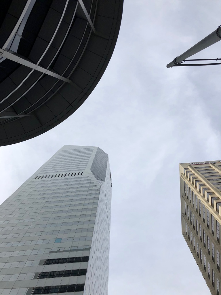 Shot from a worms eye view, three buildings and a light pole fill the corners. The top right holds the top of a light pole; the lower right has a tan colour square building, the lower left has a pale grey square building with a beveled cutout, the top left has a circular building.
