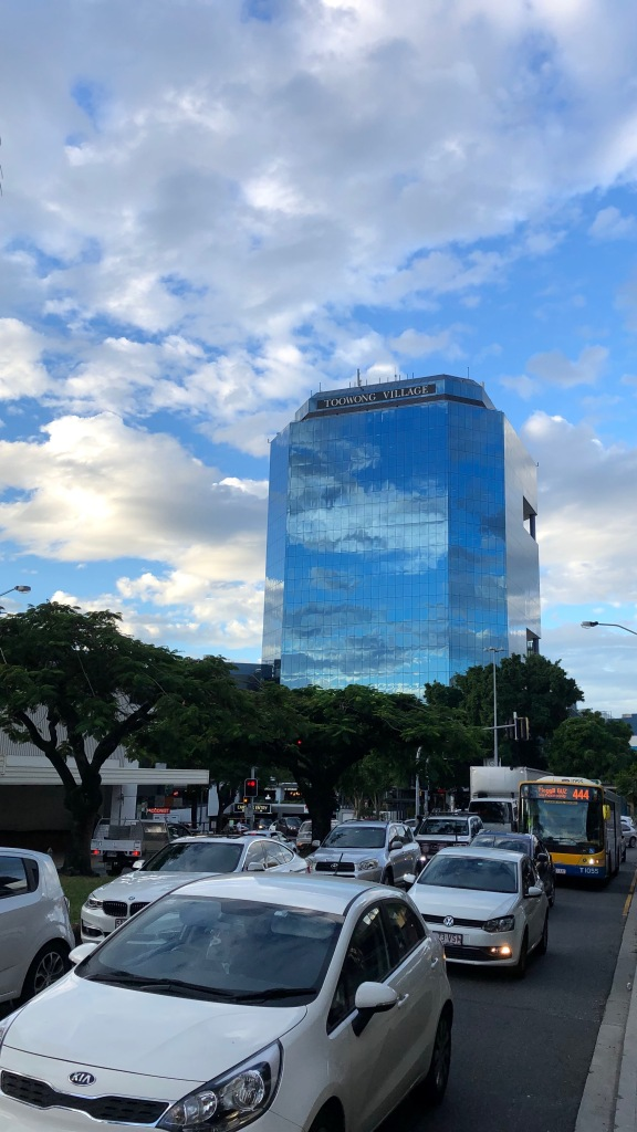 A glass panelled tower reflects a cloudy blue sky above a busy road with a treed interval.